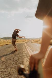 Young barefoot male skateboarder skateboarding on rural road, girlfriend watching, Exeter, Californiの写真素材 [FYI03624843]