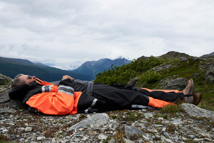Senior male hiker taking a break lying on top of mountain, side view, Valdez, Alaska, USAの写真素材 [FYI03624847]
