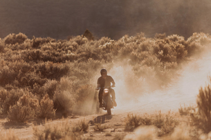 Motorbiker raising dust, Kennedy Meadows, California, USの写真素材 [FYI03624867]