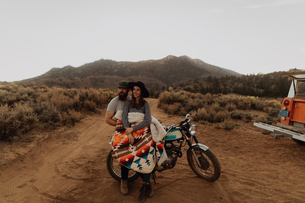 Couple relaxing on motorbike, Kennedy Meadows, California, USの写真素材 [FYI03624885]