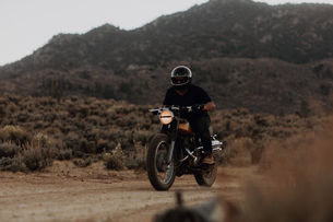 Motorbiker riding through landscape of Kennedy Meadows, California, USの写真素材 [FYI03624891]