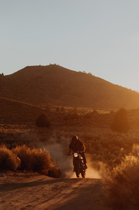 Motorbiker riding through landscape of Kennedy Meadows, California, USの写真素材 [FYI03624893]