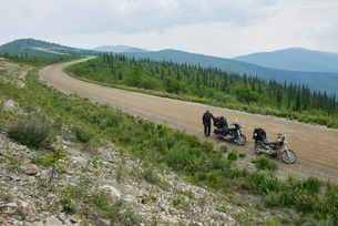 Senior male motorcyclist on rural mountain roadside with motorbike, high angle portrait, Dawson Creeの写真素材 [FYI03624910]