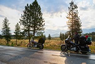 Senior male motorcyclist on rural roadside with motorbike, Dawson Creek, Canadaの写真素材 [FYI03624912]
