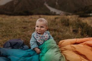Baby sitting among jackets in wilderness, Wanaka, Taranaki, New Zealandの写真素材 [FYI03624980]