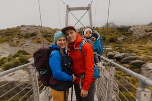 Hiker couple with baby on suspension bridge, Wanaka, Taranaki, New Zealandの写真素材 [FYI03624985]
