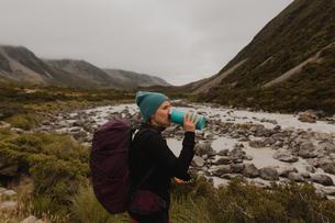 Hiker drinking, enjoying view of wilderness, Wanaka, Taranaki, New Zealandの写真素材 [FYI03625002]