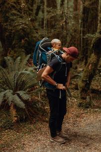 Hiker with baby exploring forest, Queenstown, Canterbury, New Zealandの写真素材 [FYI03625035]