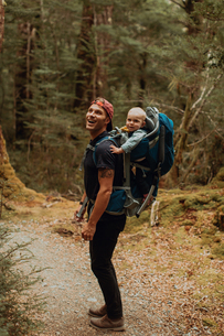Hiker with baby exploring forest, Queenstown, Canterbury, New Zealandの写真素材 [FYI03625038]