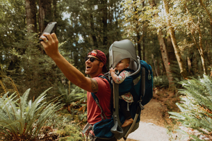 Father with baby taking selfie in forest, Queenstown, Canterbury, New Zealandの写真素材 [FYI03625079]