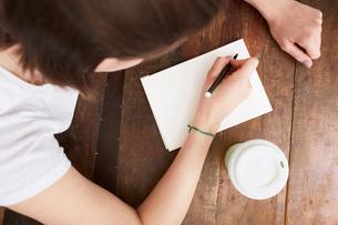 Woman writing on notebook at coffee breakの写真素材 [FYI03625207]