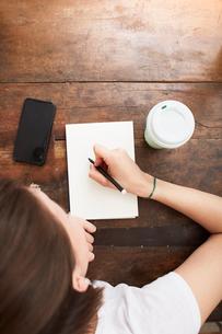 Woman writing on notebook at coffee breakの写真素材 [FYI03625208]