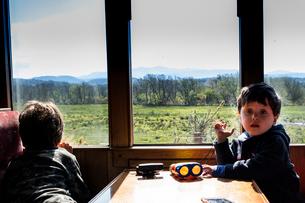 Boys travelling in train passing national park, Llanaber, Gwynedd, United Kingdomの写真素材 [FYI03625212]