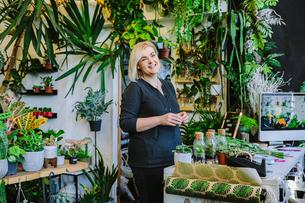 Proud owner smiling in plant nurseryの写真素材 [FYI03625300]