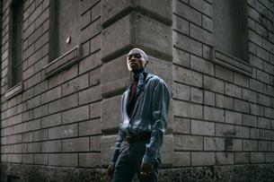 Stylish man standing at corner of period building, Milan, Italyの写真素材 [FYI03625351]