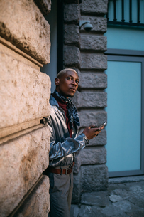 Stylish man using cellphone by period building, Milan, Italyの写真素材 [FYI03625362]