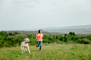 Girl running with labrador dog in scenic field landscape, Citta della Pieve, Umbria, Italyの写真素材 [FYI03625369]