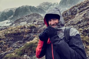 Male hiker with hood up in sleeting snow capped mountain landscape, portrait, Llanberis, Gwynedd, Waの写真素材 [FYI03625392]