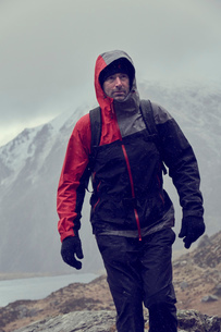 Male hiker looking up while hiking in snow capped mountains with storm clouds, Llanberis, Gwynedd, Wの写真素材 [FYI03625395]