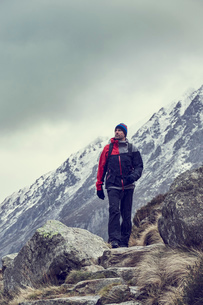 Male hiker hiking in rugged landscape with snow capped mountains, Llanberis, Gwynedd, Walesの写真素材 [FYI03625399]
