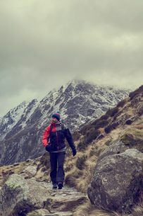 Male hiker hiking in rugged landscape with snow capped mountains, Llanberis, Gwynedd, Walesの写真素材 [FYI03625401]