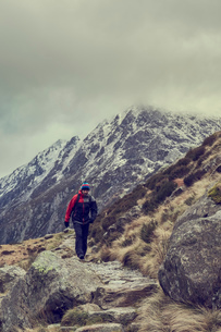 Male hiker hiking in rugged landscape with snow capped mountains, Llanberis, Gwynedd, Walesの写真素材 [FYI03625402]