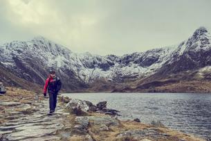Male hiker hiking alongside lake landscape with snow capped mountains, Llanberis, Gwynedd, Walesの写真素材 [FYI03625404]