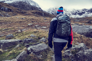 Male hiker hiking up rugged landscape with snow capped mountains, rear view, Llanberis, Gwynedd, Walの写真素材 [FYI03625410]