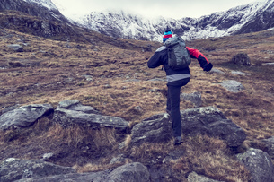 Male hiker hiking up rugged landscape with snow capped mountains, rear view, Llanberis, Gwynedd, Walの写真素材 [FYI03625411]