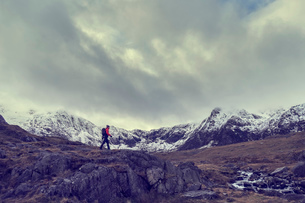 Male hiker hiking across rugged landscape with snow capped mountains, Llanberis, Gwynedd, Walesの写真素材 [FYI03625413]
