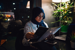 Young woman in hijab looking at menu in cafeの写真素材 [FYI03625422]