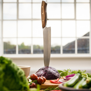 Kitchen knife stuck in red cabbage on kitchen counter, still lifeの写真素材 [FYI03625514]