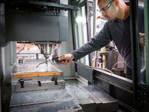 Knife factory worker spraying liquid onto machinery in workshopの写真素材 [FYI03625521]