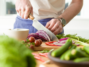 Man slicing red cabbage at kitchen counter, mid sectionの写真素材 [FYI03625523]