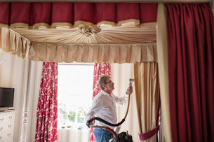 Curtain fitter using steam on material of four poster bedの写真素材 [FYI03625531]