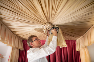 Curtain fitter making 'Ruche' on canopy of four poster bedの写真素材 [FYI03625536]