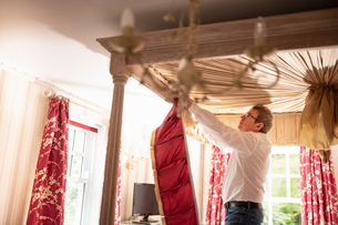 Curtain fitter fitting new pelmet to four poster bedの写真素材 [FYI03625538]