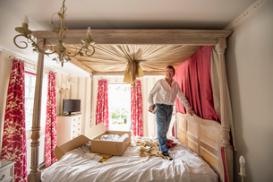 Curtain fitter putting new drapes on four poster bedの写真素材 [FYI03625541]