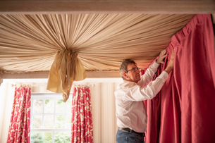 Curtain fitter fitting drapes to four poster bedの写真素材 [FYI03625542]