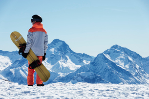 Teenage boy snowboarder looking out over landscape from snow covered mountain top, rear view, Alpe-dの写真素材 [FYI03625554]
