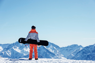 Teenage boy snowboarder looking out over landscape from snow covered mountain top, rear view, Alpe-dの写真素材 [FYI03625555]