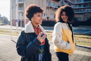 Two young women walking and talking on urban sidewalkの写真素材 [FYI03625564]
