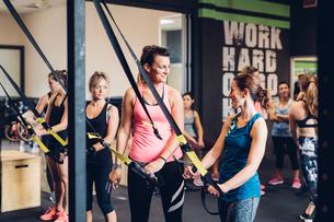 Women training in gym, chattingの写真素材 [FYI03625720]