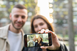 Young couple taking selfie with smartphone in cityの写真素材 [FYI03625748]