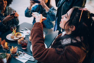 Friends taking photos of their food and drinks at outdoor cafe, Milan, Italyの写真素材 [FYI03625817]