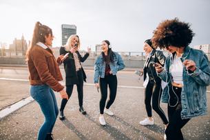 Friends dancing in street to smartphone music, Milan, Italyの写真素材 [FYI03625847]