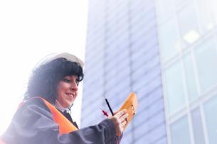 Female surveyor looking at distance meter outside office buildingの写真素材 [FYI03625880]
