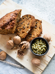 Still life of walnut and pumpkin seed cake sliced on cutting board, overhead viewの写真素材 [FYI03625887]
