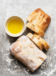 Still life of floured and unfloured ciabatta loaf on baking tray with bowl of olive oil, overhead viの写真素材 [FYI03625896]