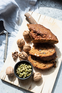 Still life of walnut and pumpkin seed cake sliced on cutting board, overhead viewの写真素材 [FYI03625898]